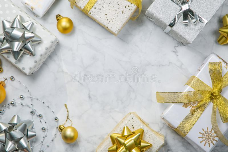 Christmas concept - silver and gold presents with confetti and ribbon. Marble background, top view stock photos