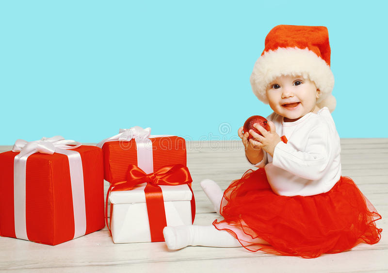 Christmas concept - smiling child in santa red hat with boxes gifts sitting on floor stock photography