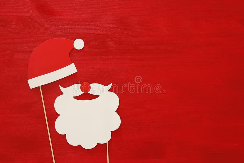 Christmas concept top view image. Santa claus beard and hat on red wooden background royalty free stock image