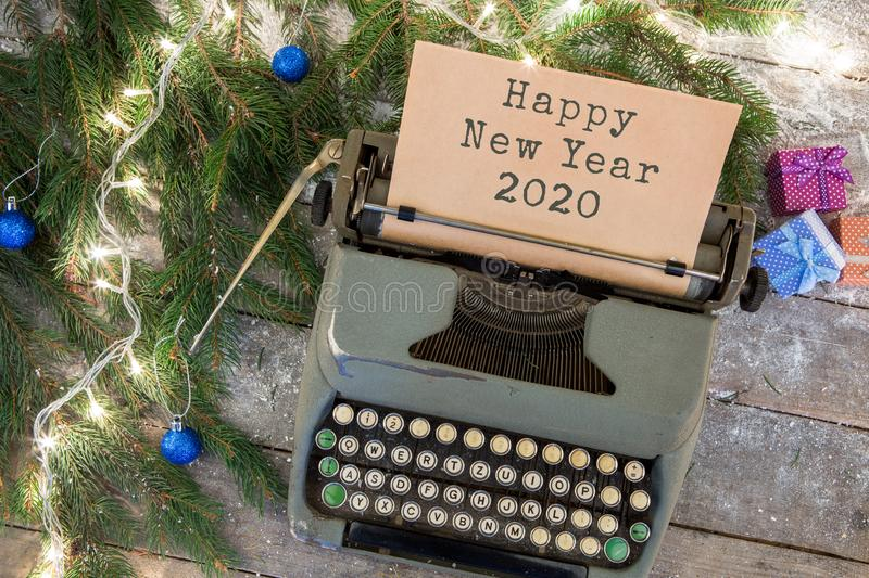 "Christmas concept - typewriter with text ""Happy New Year 2020"", spruce branches, garland, gift boxes. On wooden background stock photos"
