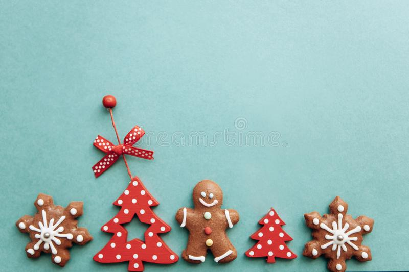 Various Christmas toys, decorations and food including gingerbread cookies on a green background. royalty free stock image