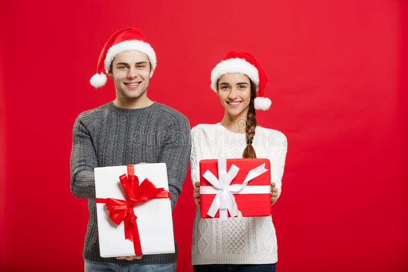 Christmas Concept - Young attractive couple giving gifts to each other celebrating in Christmas day royalty free stock photos