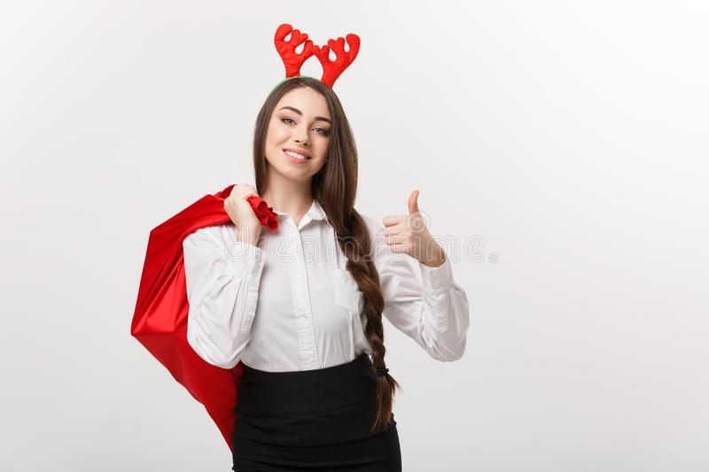 Christmas Concept - Young beautiful business woman in christmas theme holding santa red bag giving thumb up. royalty free stock photography