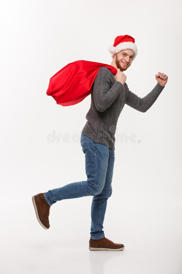 Christmas concept - Young confident beard man running and holding red big santa bag with a lot of present inside. royalty free stock photos