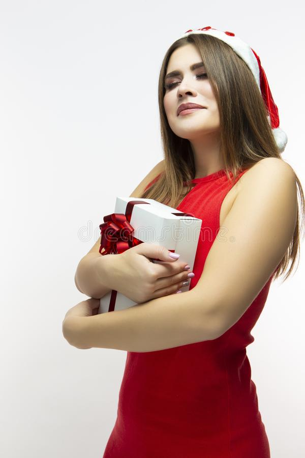 Christmas Concepts. Calm Caucasian Female In Red Dress and Santa Hat. Posing With White Gift Box Wrapped Up with Red Ribbon. royalty free stock photography