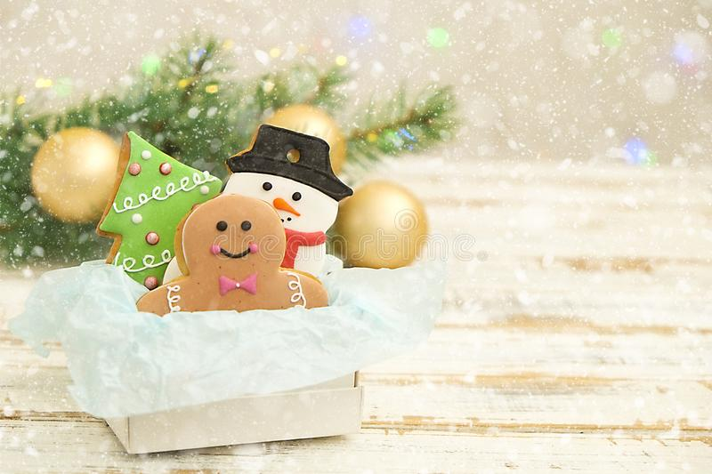 Christmas cookies in a box with gifts, lights and fir branches on white vintage wooden table. Snow effect, bokeh. Christmas composition with holiday stock photography