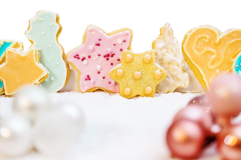 Christmas cookies with colorful frosting, baubles and icing sugar in front of white. Greeting card stock photo