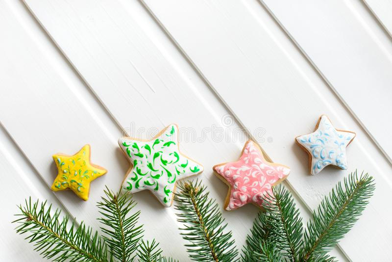 Christmas cookies with festive decoration and fir-tree branch on white wooden background. New Year and Christmas concept. Free cop stock photography