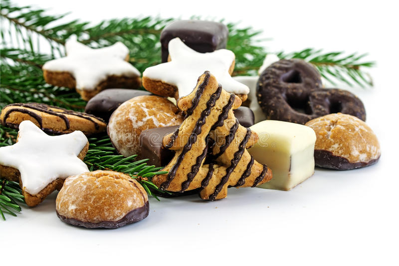 Christmas cookies and fir branches, gingerbread cakes, cinnamon. Stars and pepper nuts on white, corner background, selective focus stock images