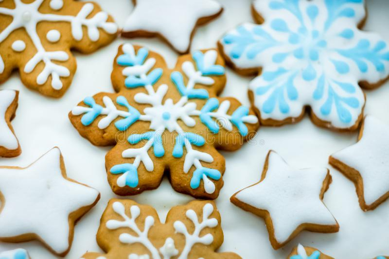 Christmas cookies in the form of snowflakes and stars decorated with icing. Different christmas ginger cookies in the form of snowflakes decorated with white and stock photos