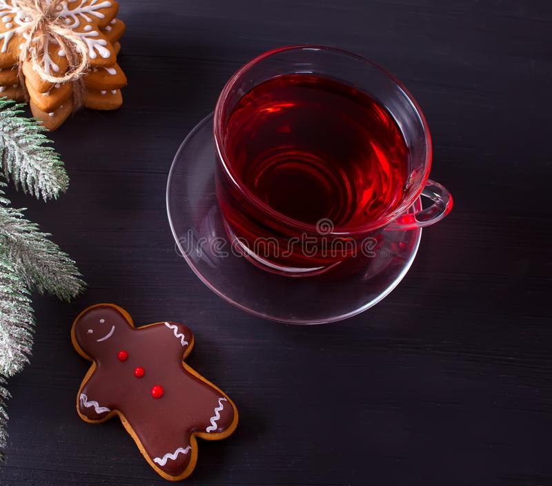 Christmas cookies funny gingerbread man and cup of tea on the black wooden table. Homemade Christmas cookies funny gingerbread man and cup of tea on the wooden royalty free stock photography