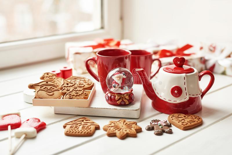 Christmas cookies and mug of hot tea, christmas time. Christmas gingerbread, candy, coffee in red cup on wooden table on frosty. Winter day window background stock image