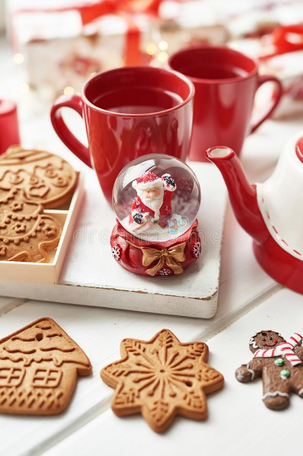 Christmas cookies and mug of hot tea, christmas time. Christmas gingerbread, candy, coffee in red cup on wooden table on frosty. Winter day window background royalty free stock photography