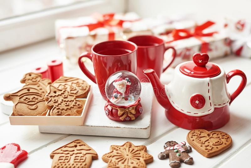 Christmas cookies and mug of hot tea, christmas time. Christmas gingerbread, candy, coffee in red cup on wooden table on frosty. Winter day window background royalty free stock photos