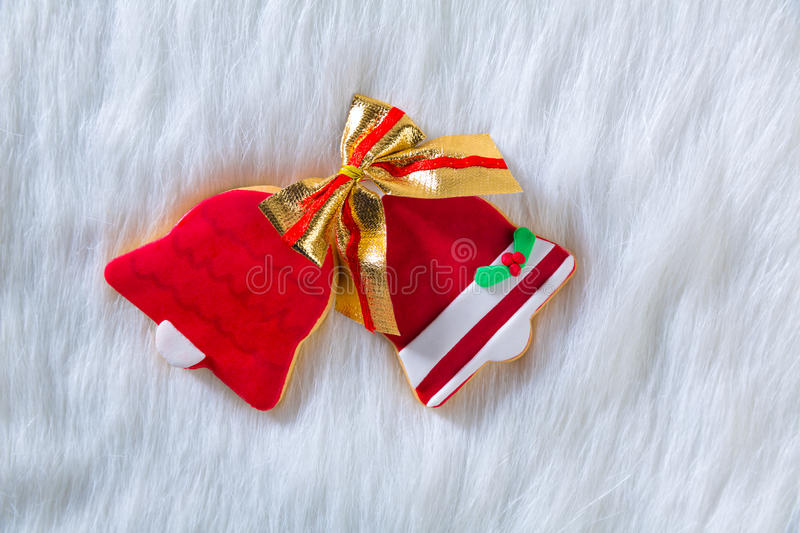 Christmas cookies red bell shape and ribbon on white fur. Christmas cookies Xmas red bell shape and ribbon on white fur background stock photos
