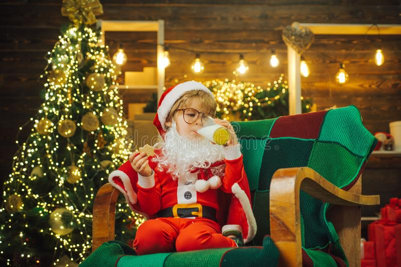 Christmas cookies. Santa child boy picking cookie. Cute Santa Claus child holding glass with milk and cookie with royalty free stock images