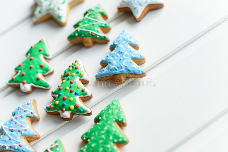 Christmas cookies in shape of fir-tree with festive decoration on white wooden background. New Year and Christmas concept. Free co. Christmas cookies in shape of stock images