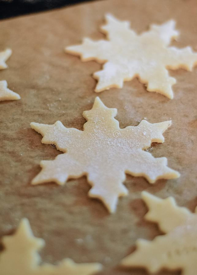 Christmas cookies thinly rolled and cut out in star shape saying. The German words Frohes Fest, which means Happy Holidays, on parchment paper on baking sheet royalty free stock image