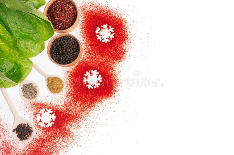 Christmas cooking - different dry spices, fresh green salad, snowflakes as decorative border, , top view. Christmas cooking - different dry spices, fresh green royalty free stock images