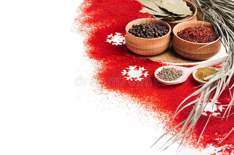 Christmas cooking - different spices in wooden bowls, snowflakes and dry twig as decorative border, , closeup. Christmas cooking - different spices in wooden stock photography