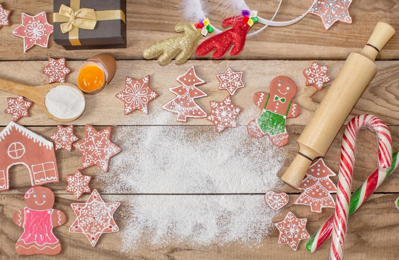 Christmas cooking. Flour for baking, eggs, ginger biscuits and Gingerbread man on wooden background. With free space for text. Festive background royalty free stock photos