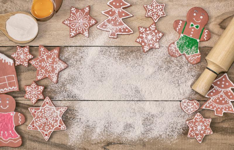 Christmas cooking. Flour for baking, eggs, ginger biscuits and Gingerbread man on wooden background. With free space for text. Festive background stock images