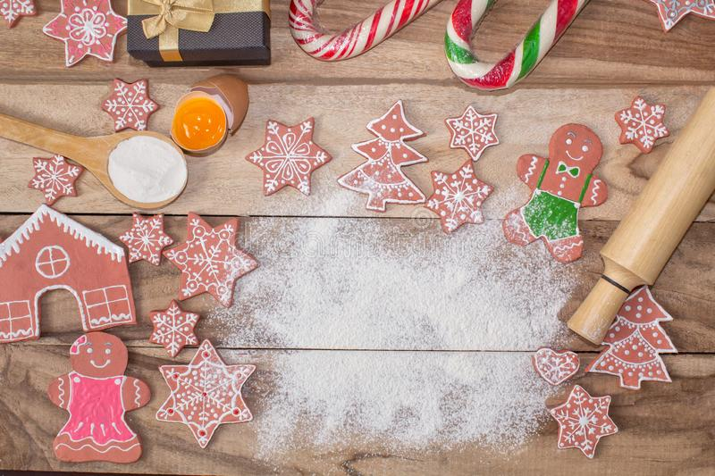 Christmas cooking. Flour for baking, eggs, ginger biscuits and Gingerbread man on wooden background. With free space for text. royalty free stock photo