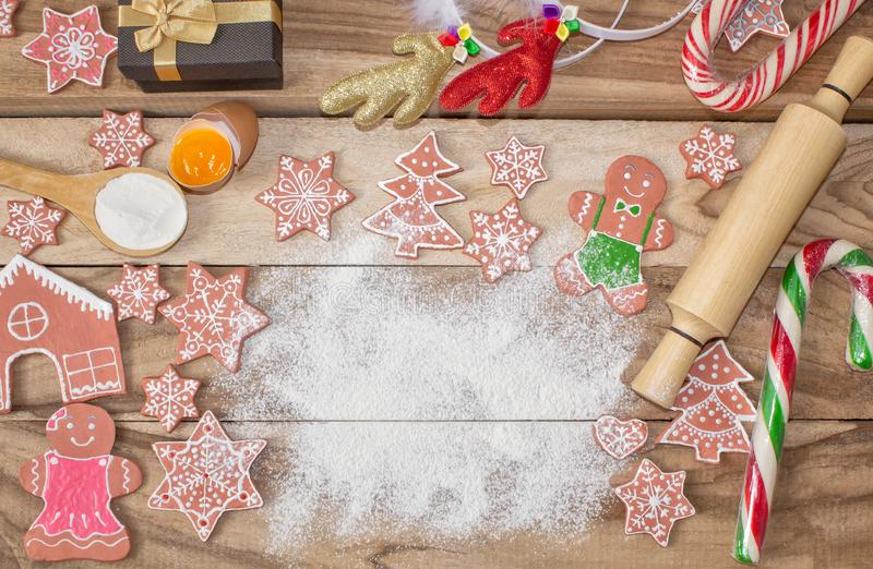 Christmas cooking. Flour for baking, eggs, ginger biscuits and Gingerbread man on wooden background. With free space for text. royalty free stock image