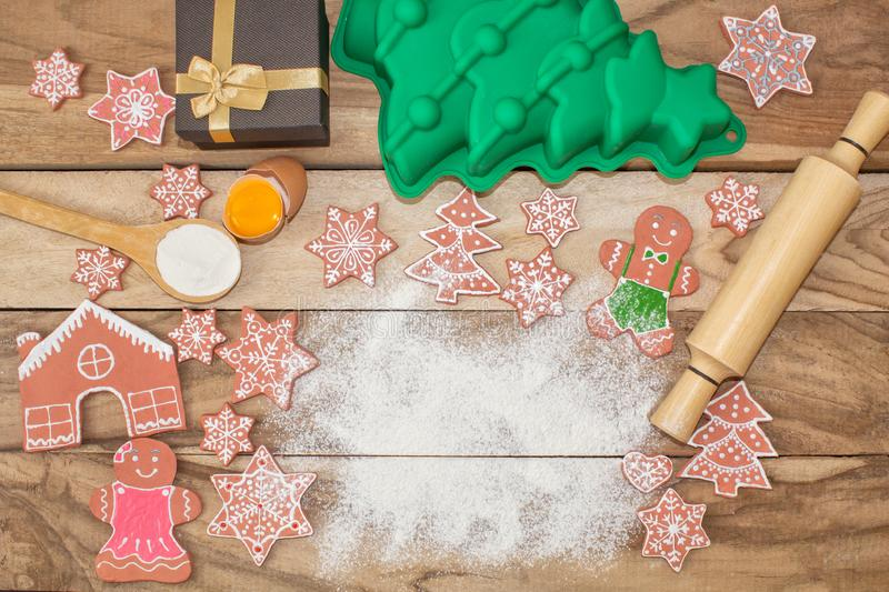 Christmas cooking. Flour for baking, eggs, ginger biscuits and Gingerbread man on wooden background. With free space for text. stock photography