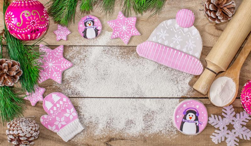 Christmas cooking. Flour for baking, rolling pin, ginger cookies in the form of penguins, mittens and hats with asterisks royalty free stock photo