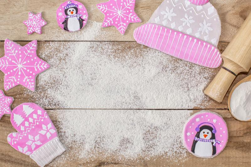 Christmas cooking. Flour for baking, rolling pin, ginger cookies in the form of penguins, mittens and hats with asterisks royalty free stock photos