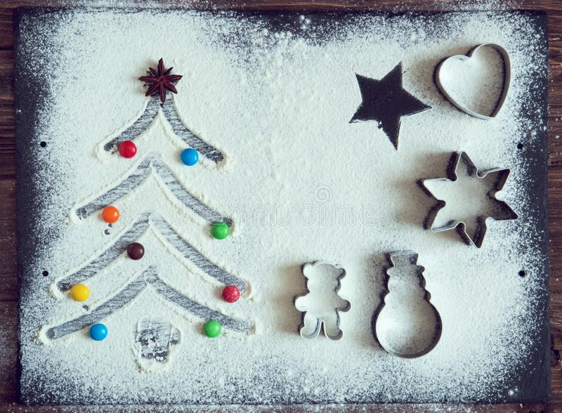 Christmas cooking. Xmas tree with decorations and candies made from flour on a dark table, ingredients for baking on dark backgrou royalty free stock images