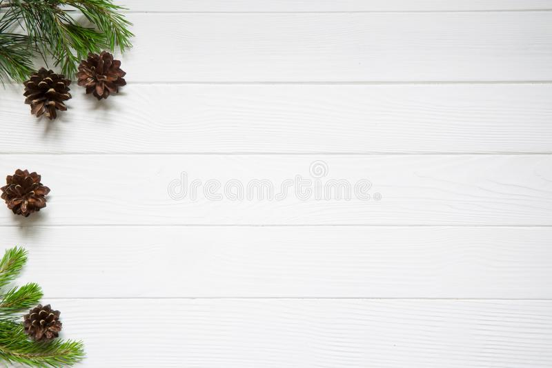 Christmas copy space. Fir tree branches with cones on white wood royalty free stock photography
