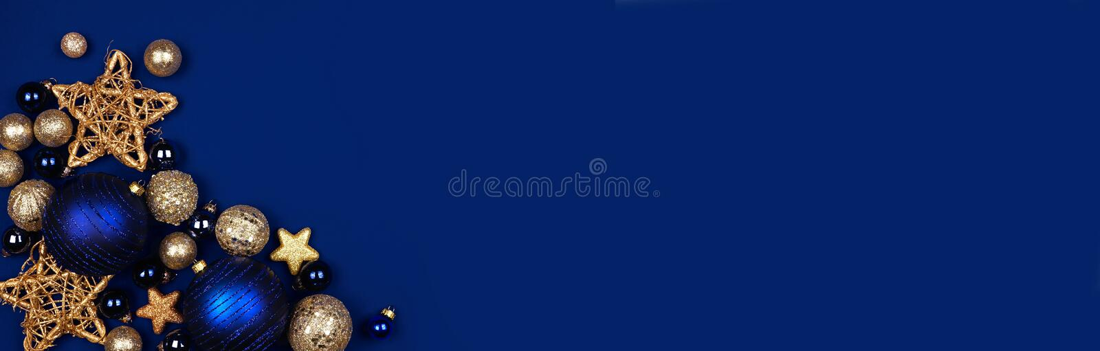 Christmas corner border banner of dark blue and gold ornaments, overhead on a midnight blue background. Christmas corner border banner of dark blue and gold royalty free stock photography