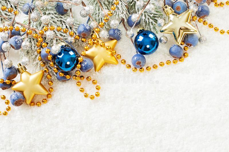 Christmas corner composition with green fir branch, gold garland, stars, blue glass baubles and berries on white snow background.  royalty free stock photography