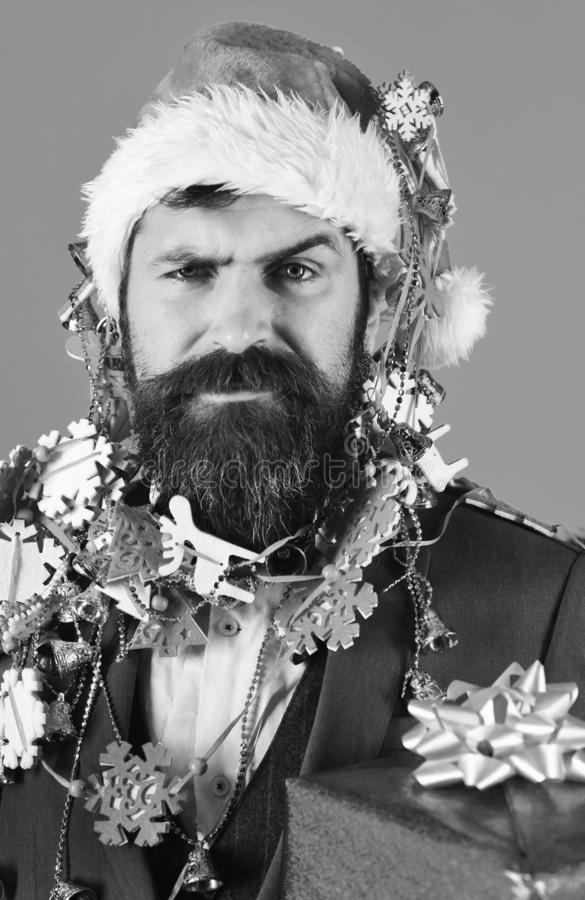 Christmas corporate party concept. Man in smart suit, Santa hat. And garlands on head on blue background. Manager with beard holds blue gift. Businessman with stock images
