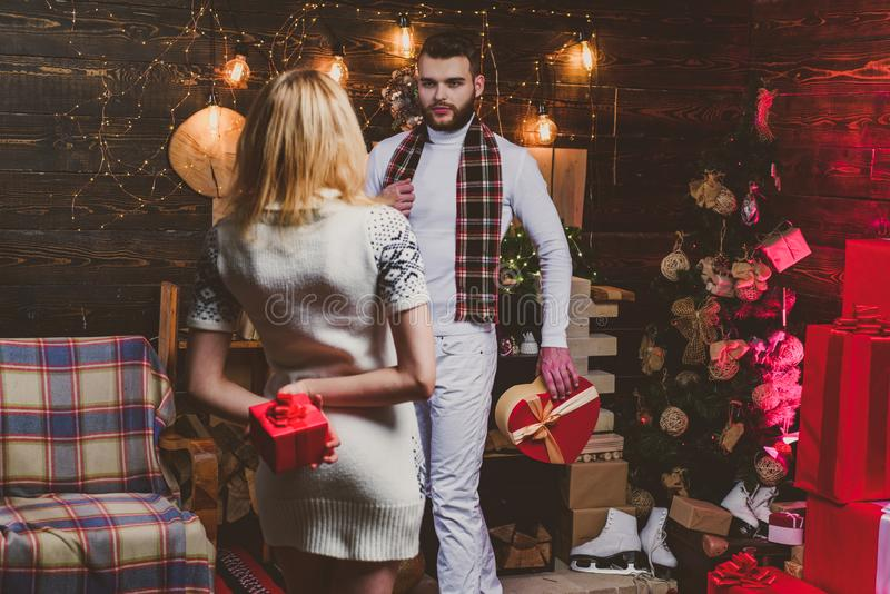 Christmas couple in love. Happy blonde young woman and man are giving Christmas gifts to each other. Lovely happy couple stock image