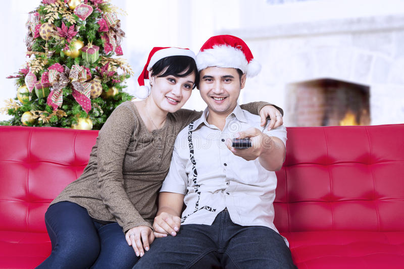 Download Christmas Couple With Santa's Hats And Holding Remote Control Stock Photo - Image: 34078272