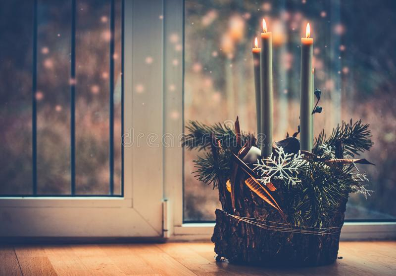 Christmas cozy home with candles at window. Advent wreath with burning candles. Winter decor interior. With warm bokeh lighting royalty free stock photography