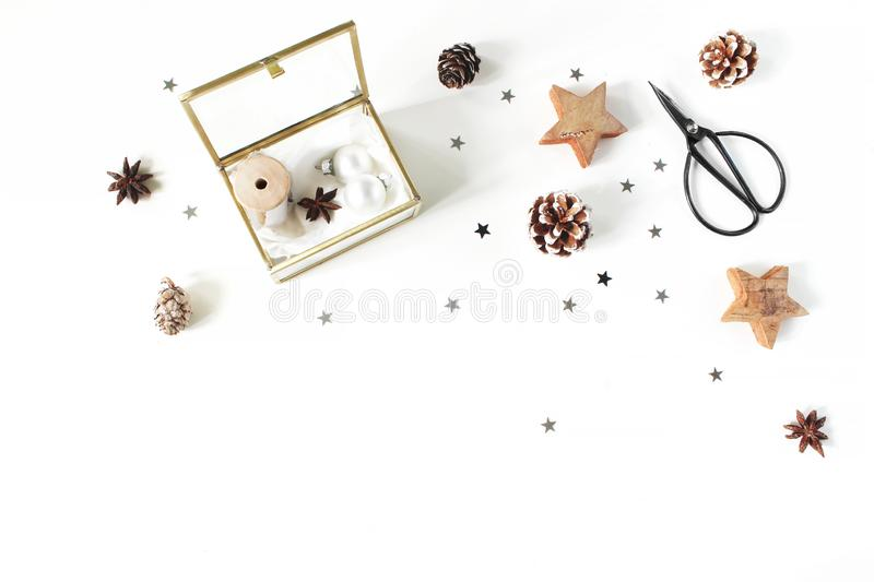 Christmas craft composition. Silk ribbons and Christmas balls in golden glass box. Vintage scissors, pine cones, silver stock photography