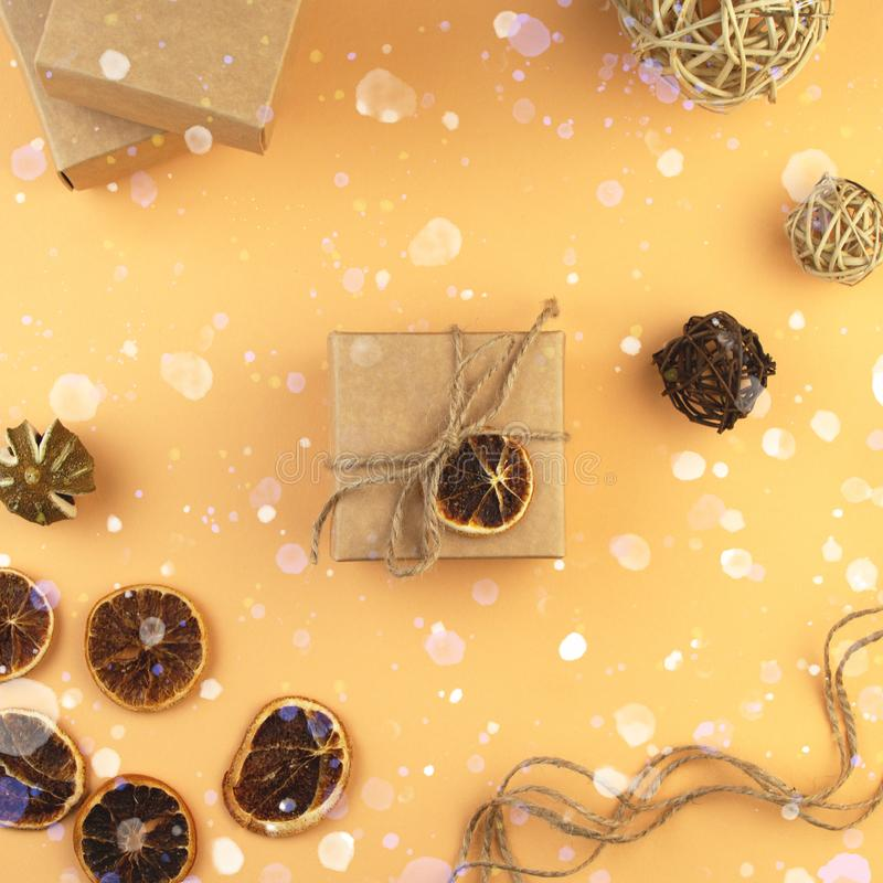 Christmas Craft gift boxes, balls from vine and slice of dry orange on pastel sand color background. Eco concept. Recycled paper and natural eco materials royalty free stock photos