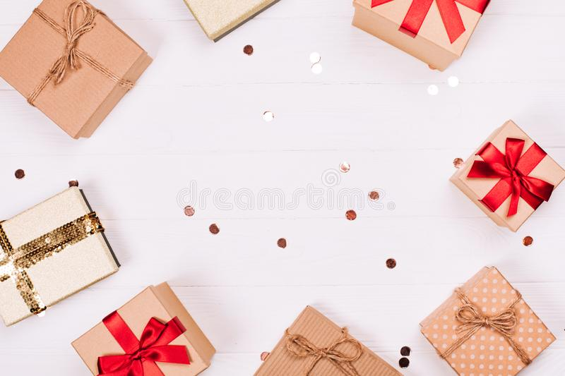 Christmas craft gift boxes create round frame on white wooden background. royalty free stock photo