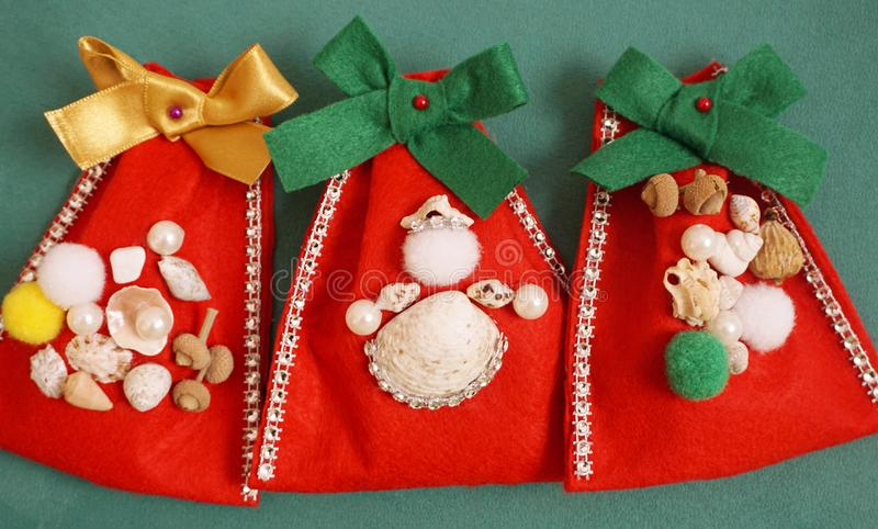 Christmas crafts. Do it yourself felt gift bags decorated with seashells and beads stock photo