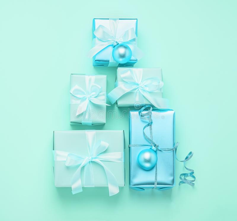 Christmas creative tree of holiday gift boxes on a pastel mint neon background. Festive minimalism concept. Flat style . Christmas creative tree of holiday gift stock photography