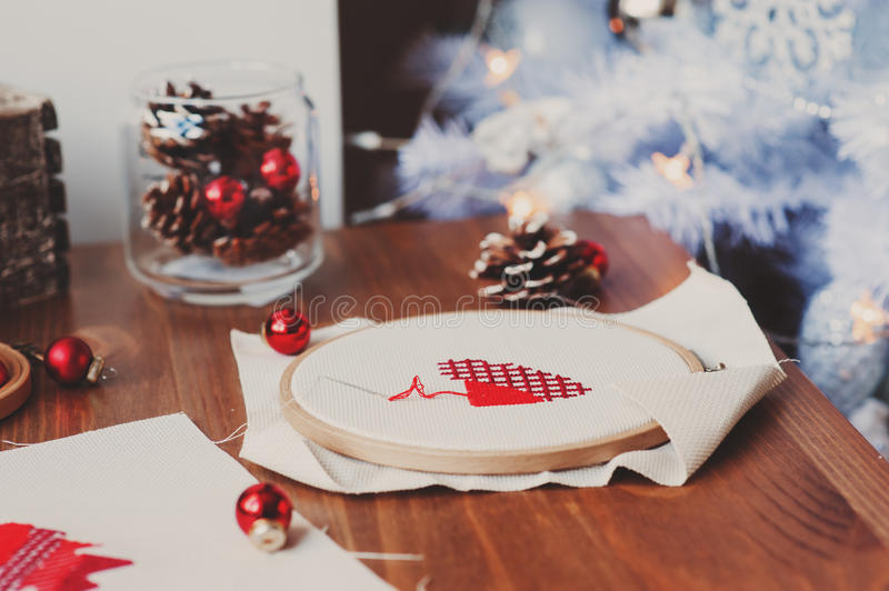 Christmas cross stitch designs and decorations on wooden table. Preparing handmade gifts for New Year and Christmas stock photography