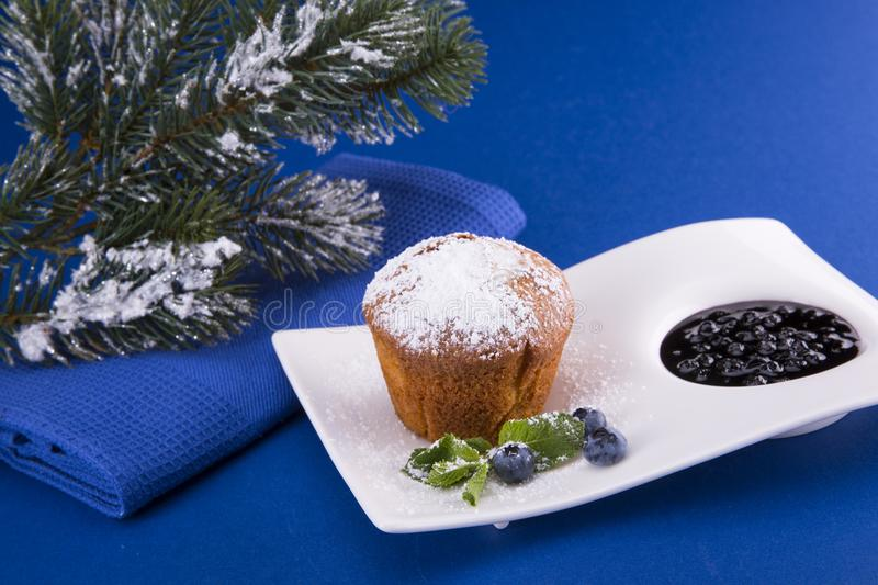 Christmas cupcake with bilberry. And Christmas tree on a blue background royalty free stock photos