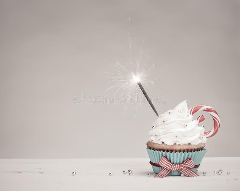 Christmas Cupcake. Christmas birthday Cupcake with a sparkler, vanilla buttercream icing and a Candy Cane royalty free stock image