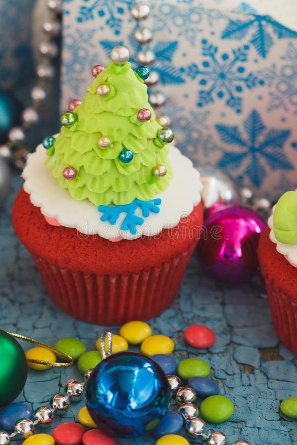 Christmas cupcake with colored decorations. Christmas Tree made from confectionery mastic, soft focus background royalty free stock images