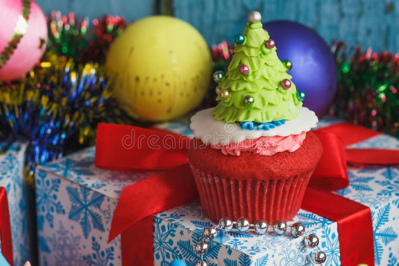 Christmas cupcake with colored decorations. Christmas Tree made from confectionery mastic, soft focus background stock photography
