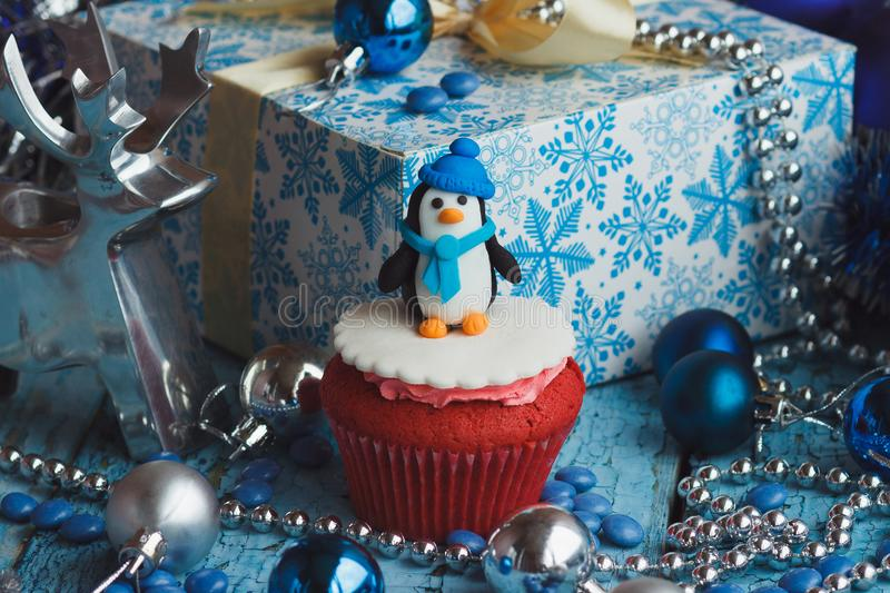 Christmas cupcake with colored decorations. Penguin made from confectionery mastic, soft focus background royalty free stock images